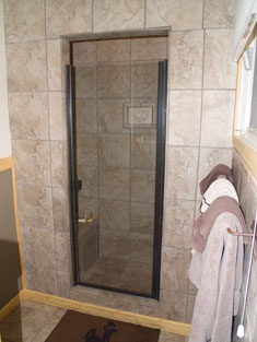 Bathroom with tile walls, and large, walk in shower.