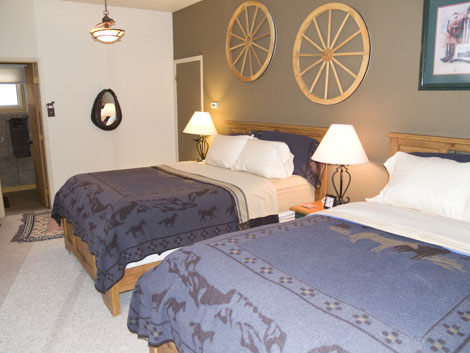 The room with 2 queen size beds, and western themed art and decorations.