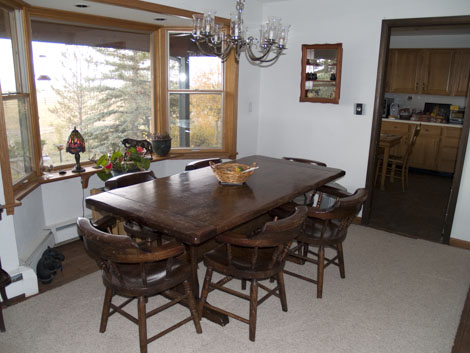 Large dining room table with a picture window.